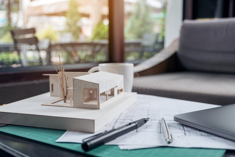 An architects designed architecture model with shop drawing paper. And laptop on table royalty free stock photo