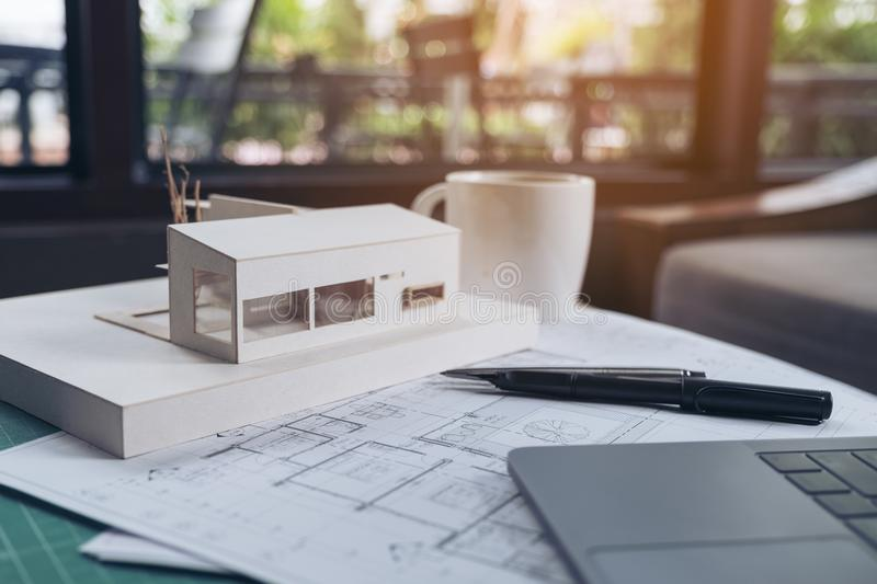 An architects designed architecture model with shop drawing paper. And laptop on table royalty free stock photography