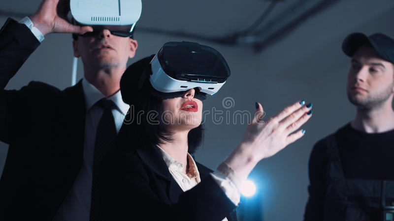 Architects and designers in VR headsets on the site. The people with virtual reality headsets on a construction site. The women shows to group of architects and royalty free stock image