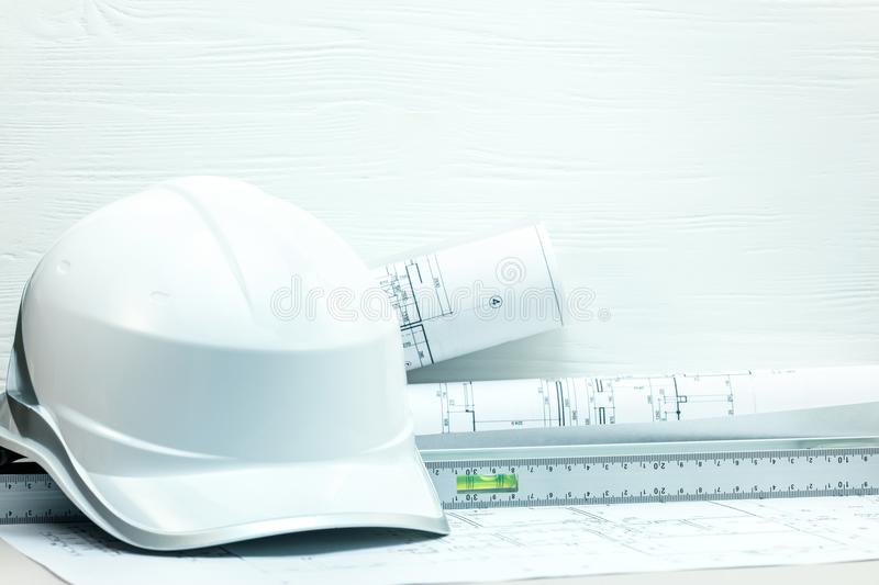 Architects desk with blueprints, protective helmet, measuring to. Ols. construction concept background stock photo