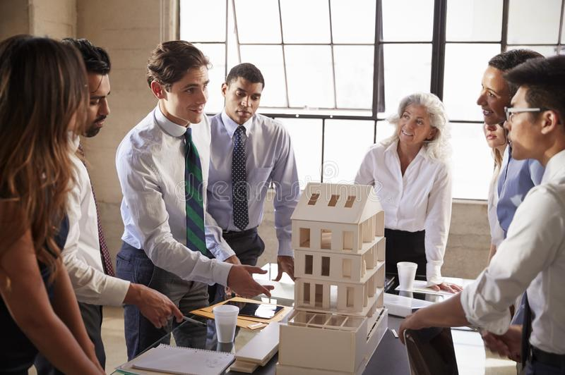 Architects discussing the scale model of a building stock images