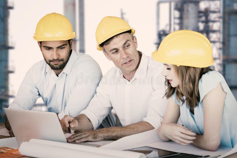 Composite image of architects discussing while sitting at table royalty free stock photography
