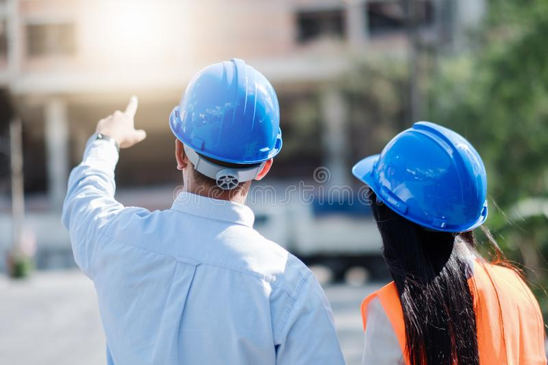 Architects And Engineer at a construction site looking at blueprints and pointing royalty free stock image