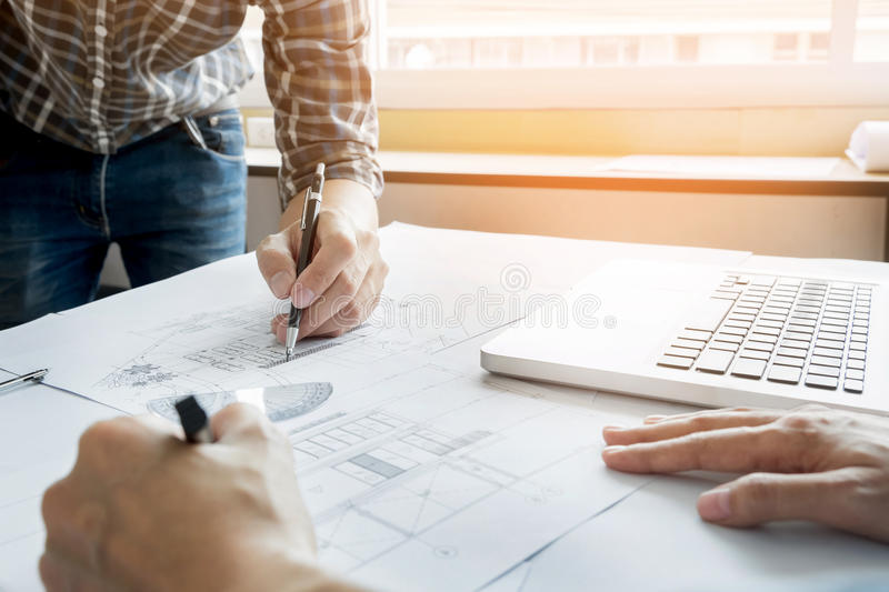 Architects engineer discussing at the table with blueprint - Closeup on hands and project print, Team group on construciton site stock images