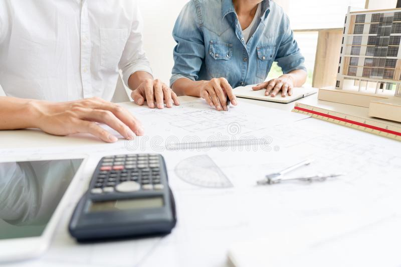 Architects engineer discussing at the table with blueprint, teamwork and work flow construction concept royalty free stock image