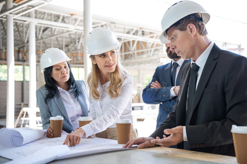 Architects in formal wear working with blueprints at construction area. Pensive architects in formal wear working with blueprints at construction area royalty free stock image