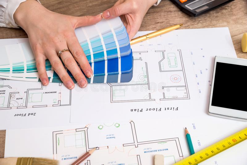 Architects hands working with drawing sketch home, color sample. And other working tools stock images