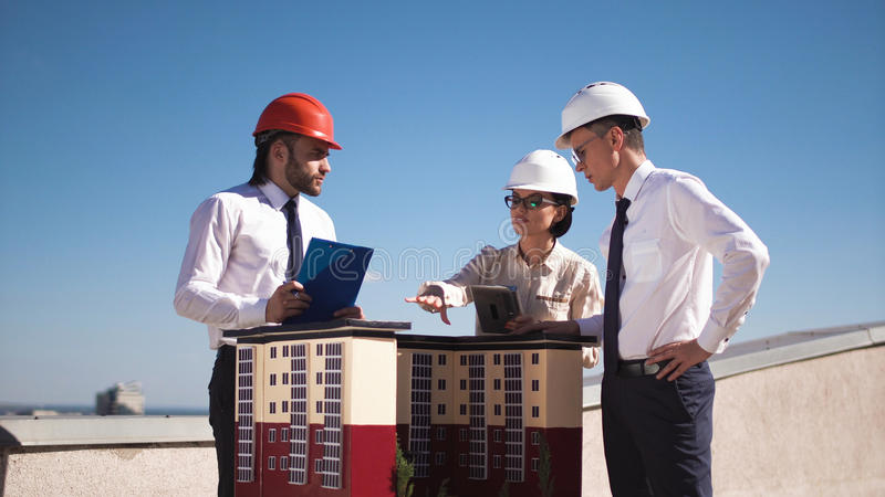 Architects in helmets at house model royalty free stock image