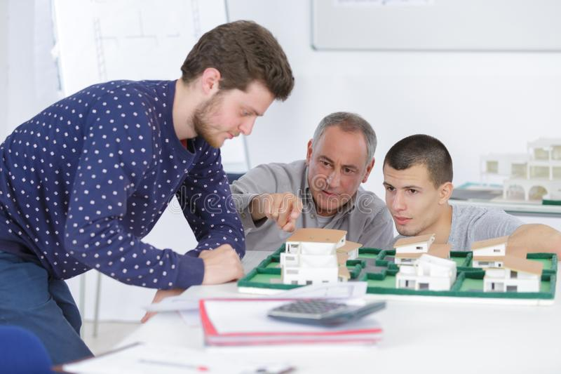 Architects with house model and blueprint working in office royalty free stock image