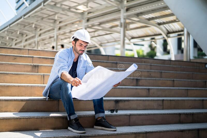 Architects looking at the blueprint paper and thinking about planning during the break per stock photo