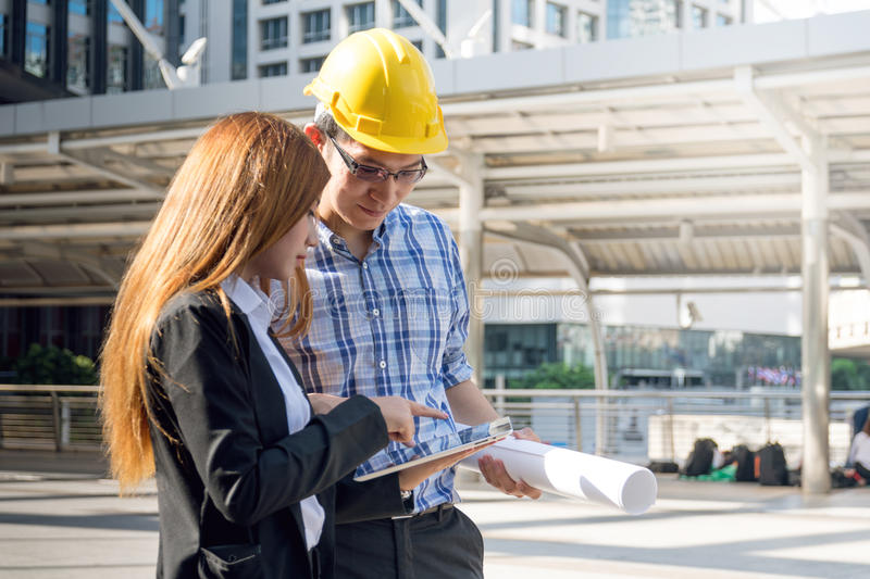 Architects are planning new project. They are working at constructions site. stock photo
