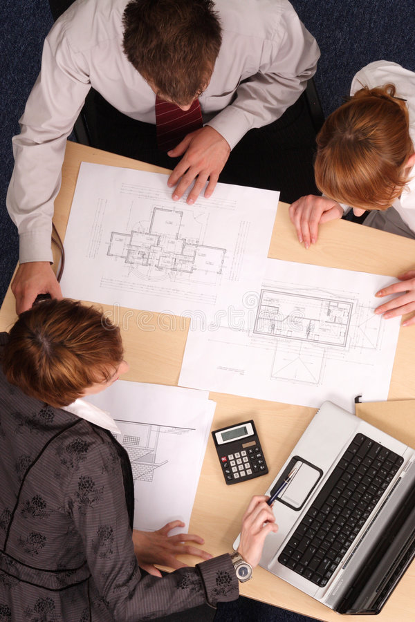 Architects studying plans. A team of architects designing and studying a building plan royalty free stock images