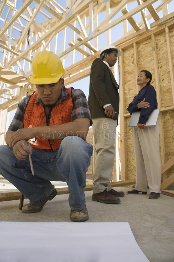 Architects Talking And Worker Looking At Blueprints royalty free stock image