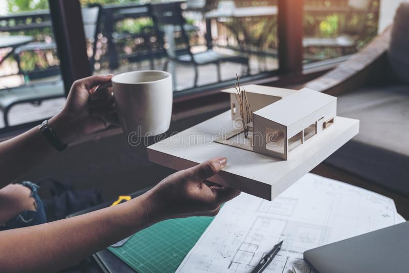 An architects thinking and designing mass model while drinking hot coffee with shop drawing paper. And laptop on table stock image