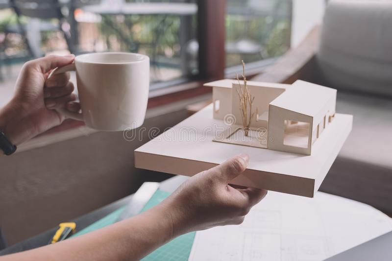 An architects thinking and designing mass model while drinking hot coffee with shop drawing paper and laptop. On table stock image