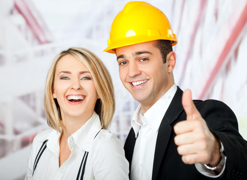 Architects thumbs up. Male and female architects smiling at camera, man wearing hardhat and showing thumbs up stock image