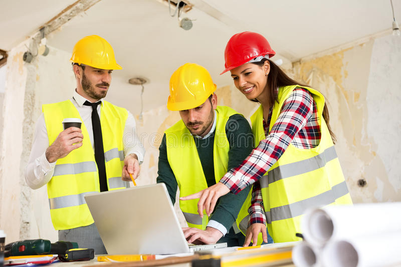 Architects using laptop at construction site royalty free stock photography