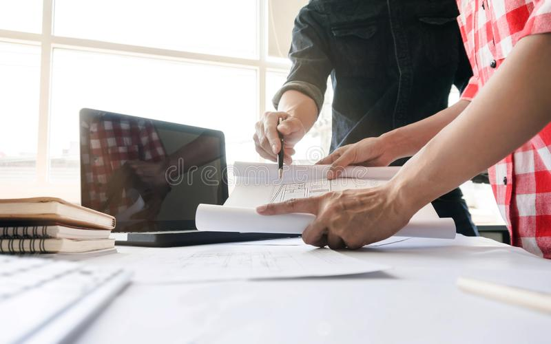 Architects working on blueprint building project together. engineer Team work concept royalty free stock images