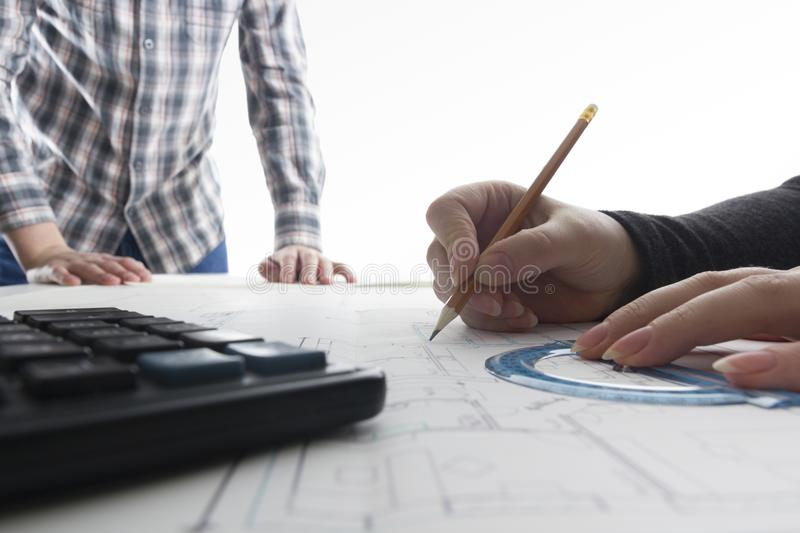 Architects working on blueprint real estate project architect download architects working on blueprint real estate project architect workplace architectural project malvernweather Choice Image