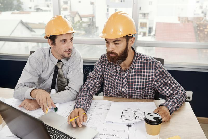 Architects working with laptop and blueprint stock images