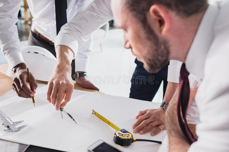 Architects working on plan together in modern office. Team of architects working on plan together in modern office stock images