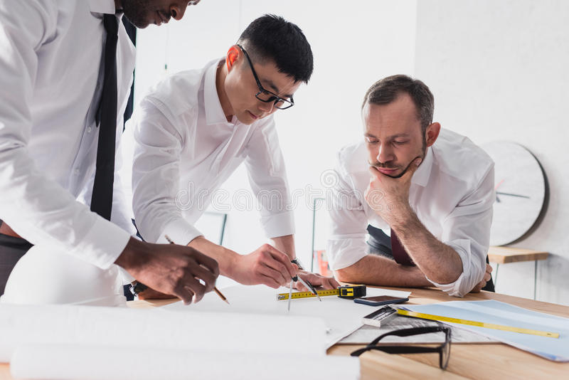Architects working on plan together in modern office. Team of architects working on plan together in modern office stock photo