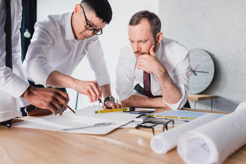 Architects working on plan together in modern office. Team of architects working on plan together in modern office royalty free stock photography