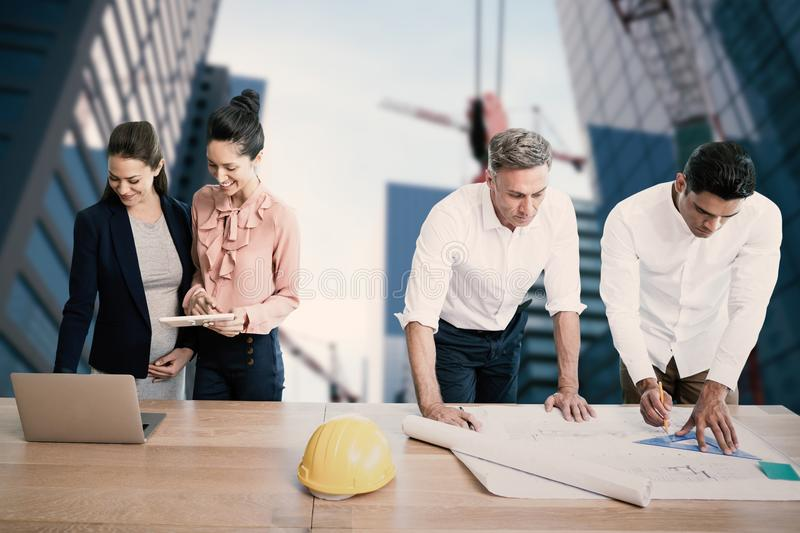 Composite image of architects working at table. Architects working at table against composite image of studio shoot of a crane royalty free stock photos