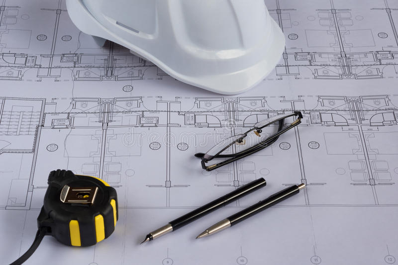 Architects workplace - architectural blueprints with measuring tape, safety helmet, glasses and propelling pencil on table. Top vi. Ew stock photography