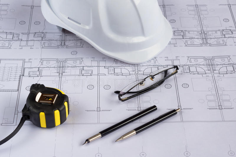 Architects workplace - architectural blueprints with measuring tape, safety helmet, glasses and propelling pencil on table. Top vi. Ew stock photos