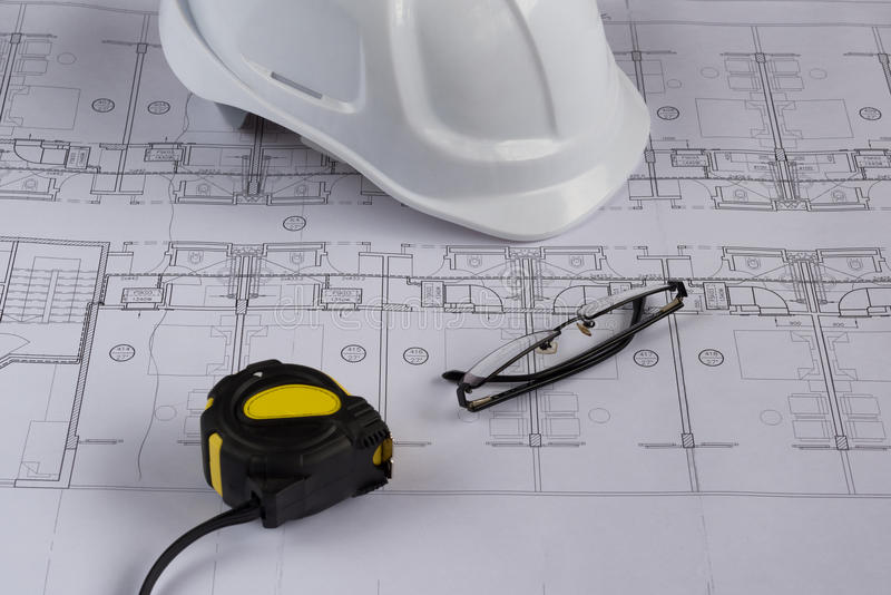 Architects workplace - architectural blueprints with measuring tape, safety helmet, glasses and propelling pencil on table. Top view stock image