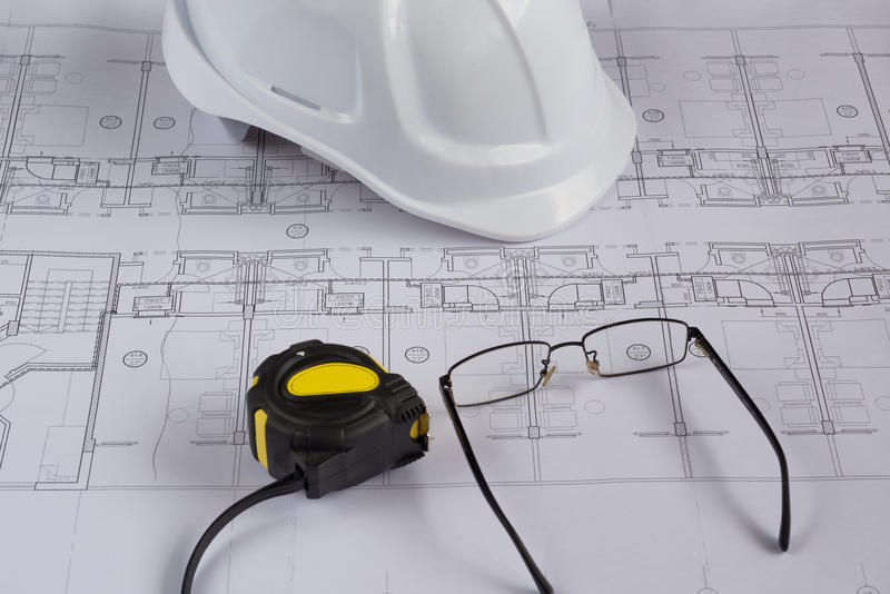Architects workplace - architectural blueprints with measuring tape, safety helmet and glasses on table. Top view. Architects workplace - architectural royalty free stock photos