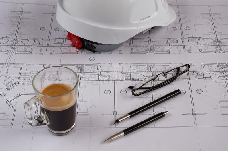 Architects workplace - architectural blueprints with safety helmet, glasses, coffee and propelling pencil on table. Top view. Architects workplace royalty free stock photos