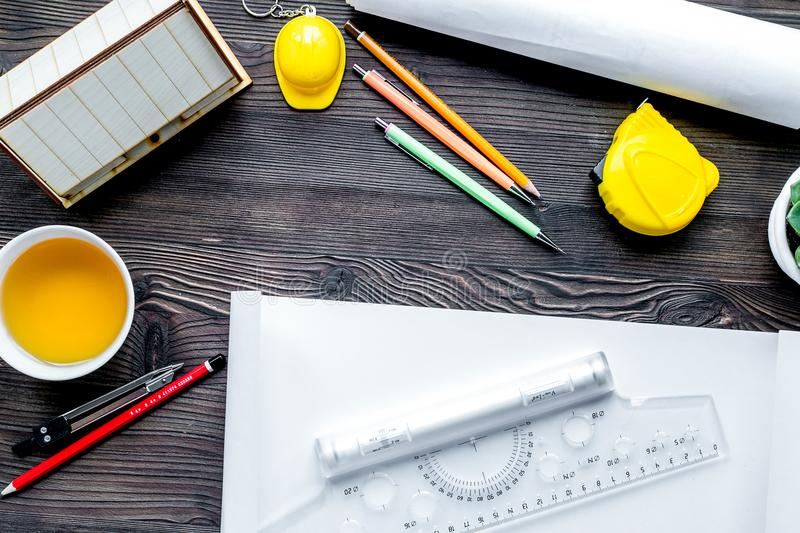Architects workplace with tools on wooden background top view. Architects workplace with constructor tools with cup of tea and projects on wooden table stock image