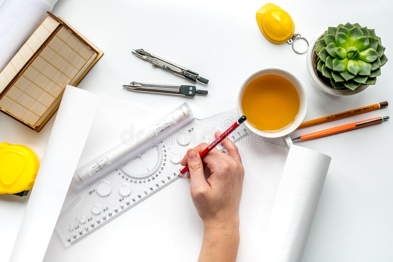 Architects workplace with tools on white background top view. Architects workplace with constructor tools with miniature and hands on white table background top stock image