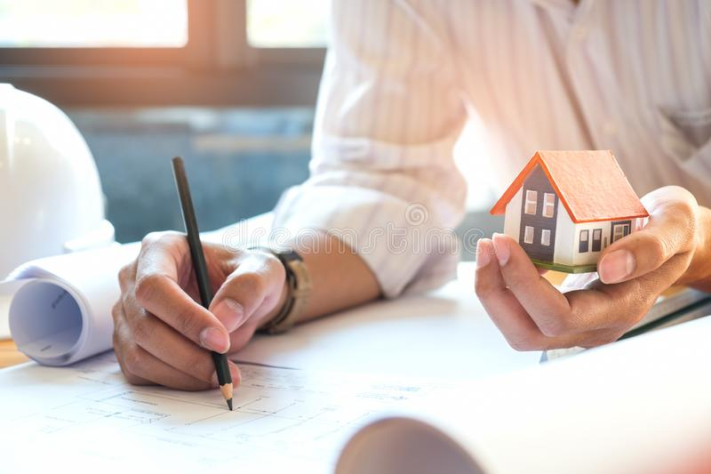 Architects are writing home,model house on other hand. Architects are writing home,model house on other hand,Architects wear white shirts and mdel house with royalty free stock photos