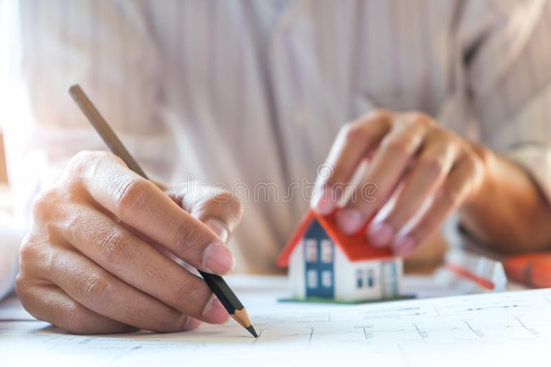 Architects are writing home, other hand captures the model house. Architects are writing home, other hand captures the model house, Architects wear white shirts royalty free stock images