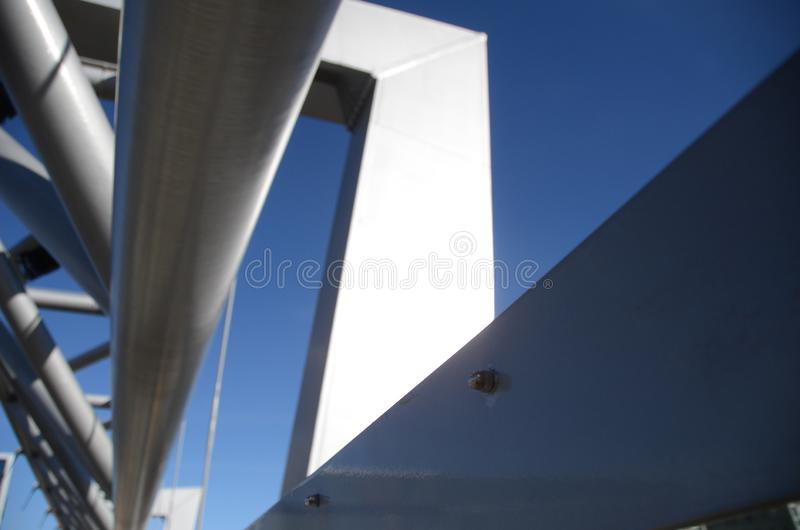 Architecturaal detail van witte brug op blauwe hemel en bouten in voorgrond stock fotografie