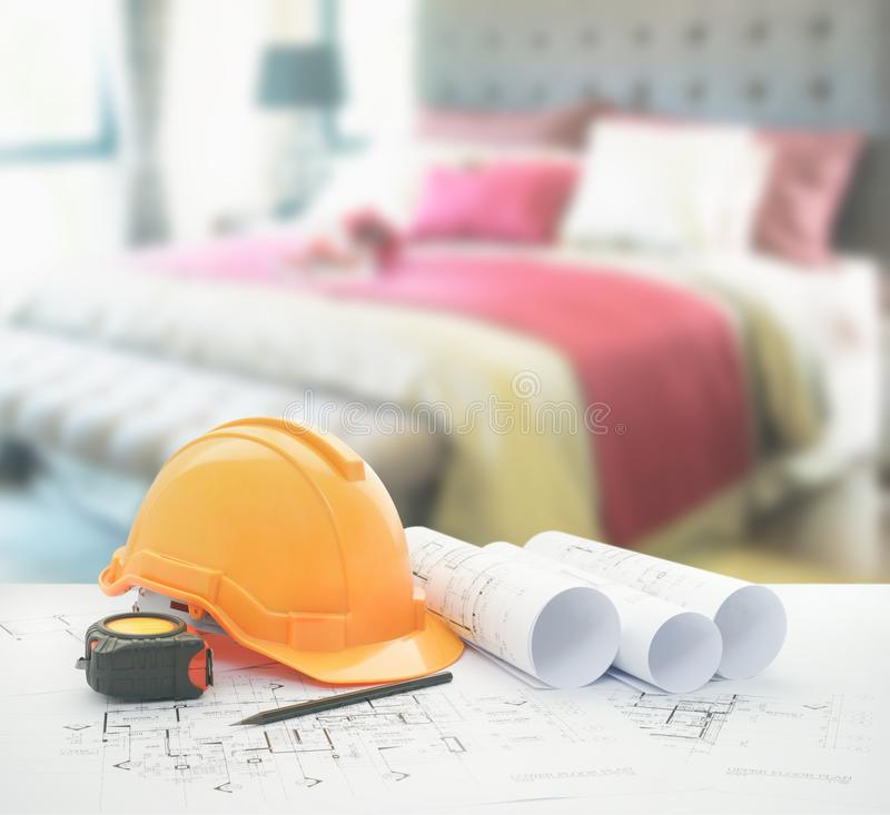 Architectural blueprint with safety helmet and tools over bedroom with red scheme color decoration stock image