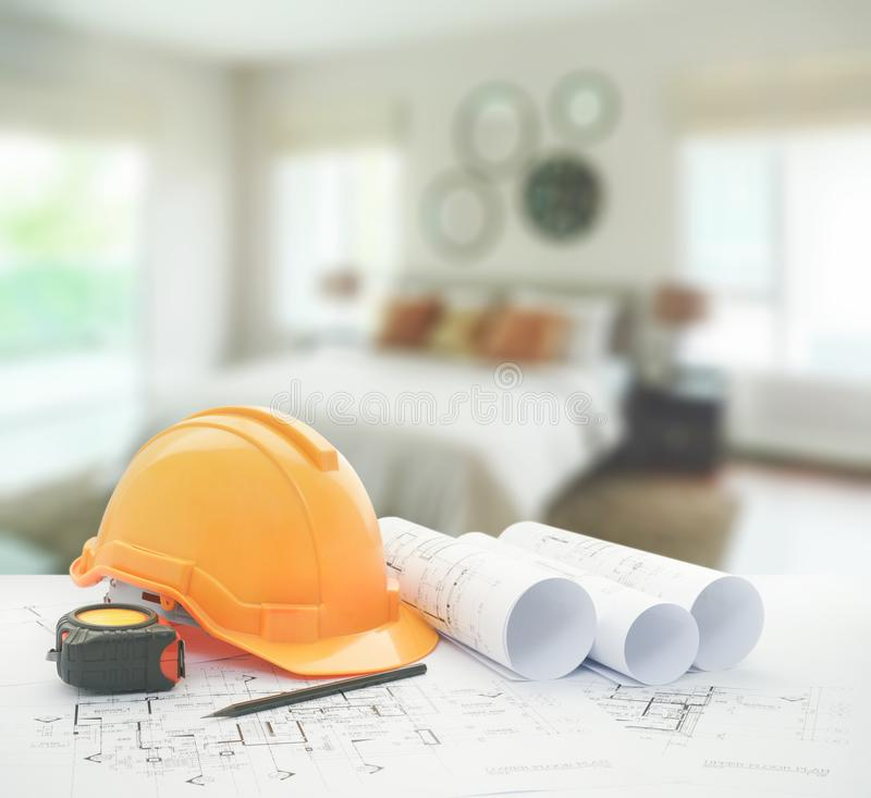 Architectural blueprint with safety helmet and tools over modern bedroom interior royalty free stock photography