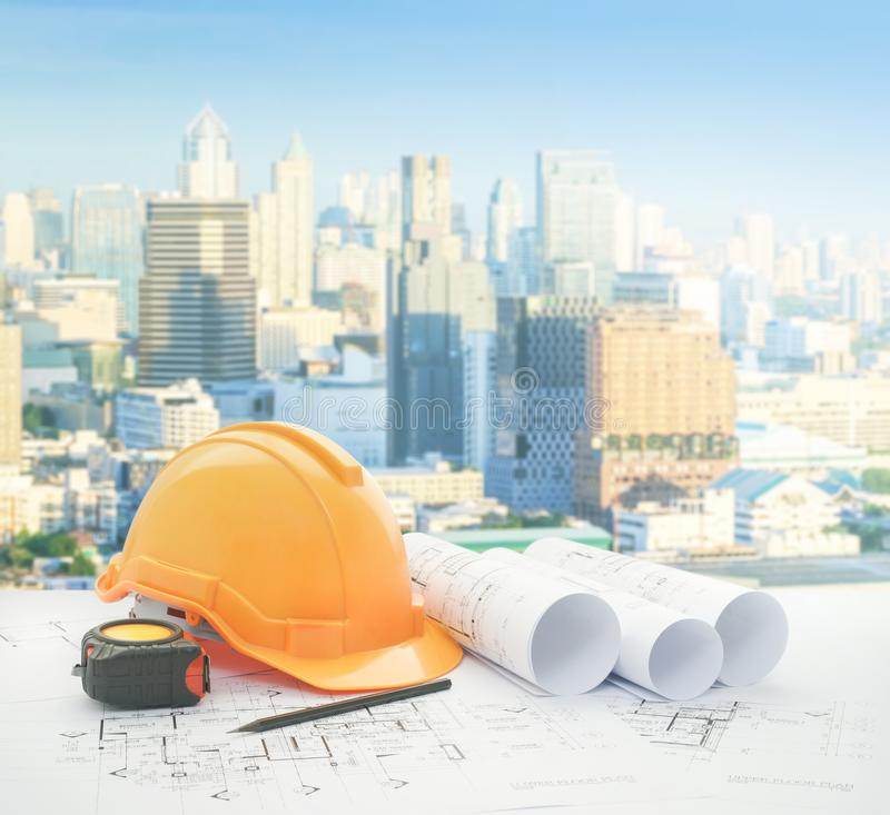 Architectural blueprint with safety helmet and tools over modern business district with high building royalty free stock image