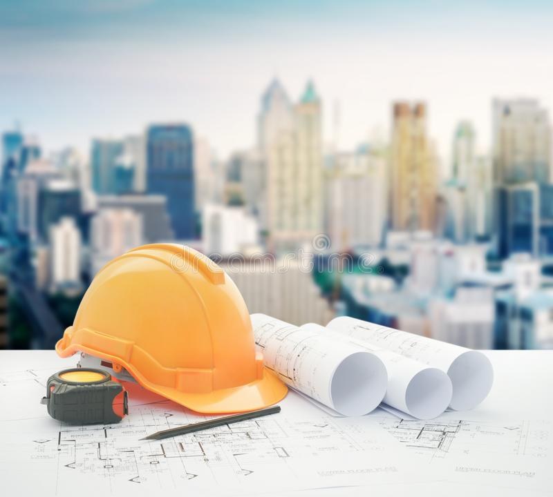 Architectural blueprint with safety helmet and tools over modern high building stock photography