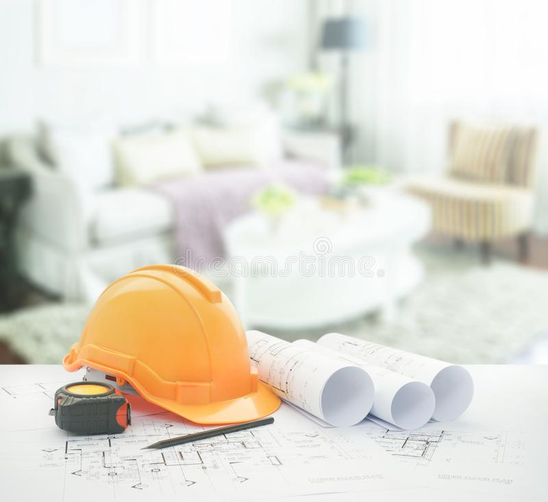 Architectural blueprint with safety helmet and tools over vintage style living room interior stock photos