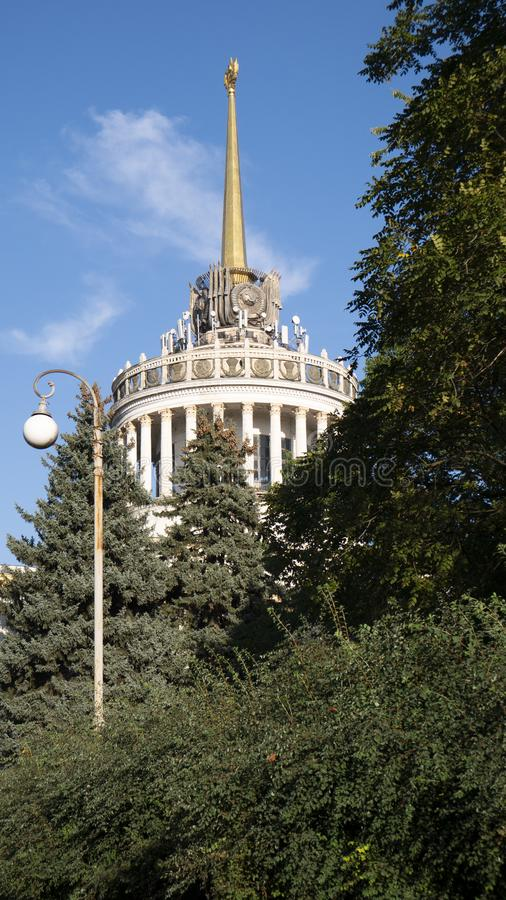 Architectural building in the trees. Blue sky in the background. Street lamp. Spire and tower building stock images