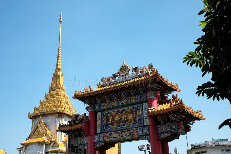 Architectural detail of Buddhist temple, Wat Traimit and Chinatown Gate over blue sky in Bangkok, Thailand royalty free stock images