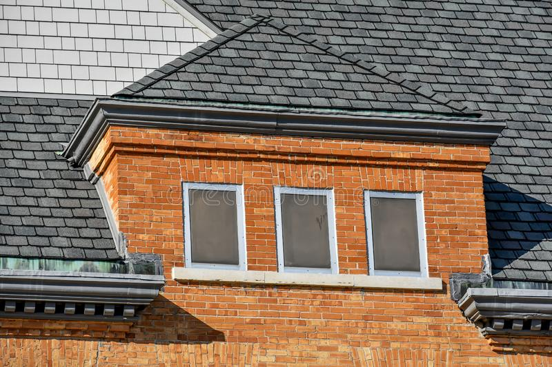 Architectural Details, Brick Building, Roof Lines. The architectural details of an old brick building with differing roof lines at an old school building in stock photography