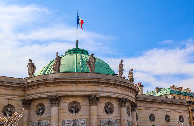 Architectural details of a historic building facade with a french flag on the roof. Paris, France. April 2019 royalty free stock images