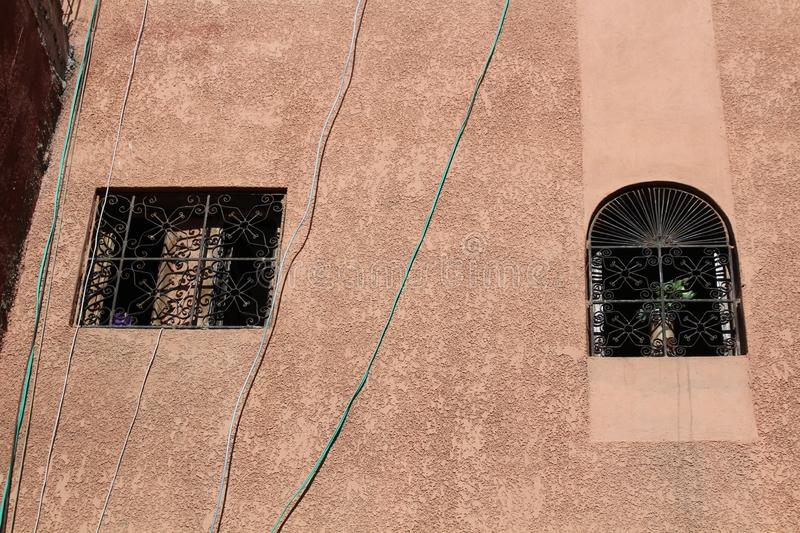 Two different windows - square window and an arched window in historical centre of Marrakesh royalty free stock photos
