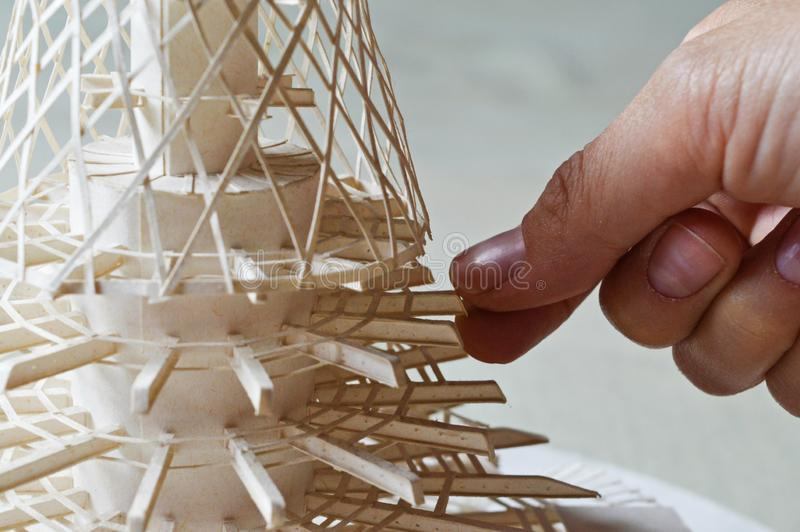 Architectural model. Made of hard white paper. Reduced model of construction of TV transmitter and hotel Ještěd. Liberec, Czech Republic. Hand of builder stock photos