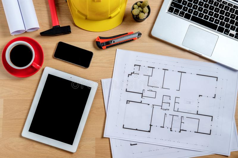 Architectural office desk with laptop. Smart phone,tablet,cup of coffee and engineer equipment.Top view background construcion project idea concept stock photos